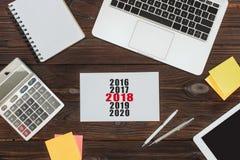 vue supérieure des dispositifs numériques, des fournitures de bureau et du calendrier 2018 photo libre de droits