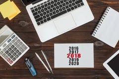 vue supérieure des dispositifs numériques, des fournitures de bureau et du calendrier 2018 photos stock