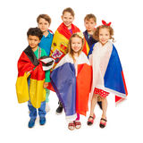 Vue supérieure des enfants enveloppés dans les drapeaux européens de nations Photographie stock