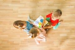 Vue supérieure des enfants jouant avec le conseil occupé à la maison photos libres de droits