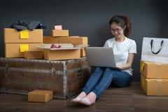 Vue supérieure des femmes travaillant l'ordinateur portable de la maison sur le plancher en bois avec le colis postal, vendant le photo libre de droits