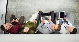 Vue supérieure des filles et du type attirants à l'aide d'un ordinateur portable, regardant l'appareil-photo et souriant tout en  image stock
