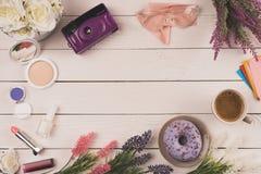 Vue supérieure des fleurs, de l'appareil-photo, des cosmétiques, de la tasse de café et du beignet Photographie stock libre de droits