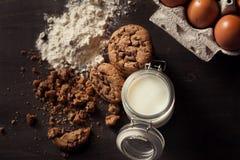 Vue supérieure des gâteaux aux pépites de chocolat faits maison avec la bouteille de lait, de farine blanche, d'oeufs frais et de photo libre de droits