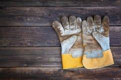 Vue supérieure des gants usés de travail et des outils assortis de travail au-dessus du fond en bois image stock