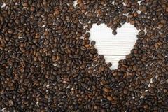 Vue supérieure des grains de café dans la forme de coeur sur la surface en bois Photographie stock libre de droits
