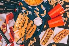 vue supérieure des hot-dogs, des tasses en plastique, des arachides, des bouteilles à bière, de la boule de base-ball et du gant  Photographie stock