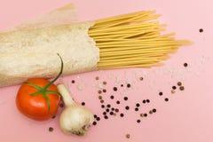 Vue supérieure des ingrédients italiens des tomates de pâtes et de légumes, pâtes, ail, poivre, fromage, épices sur un fond bleu image stock