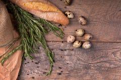 Vue supérieure des ingrédients rustiques Feuilles fraîches de baguette et de romarin sur un fond en bois Oeufs de caille complète Photos libres de droits