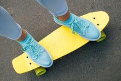 Vue supérieure des jambes femelles dans des jeans sur une planche à roulettes jaune Photographie stock libre de droits