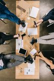 Vue supérieure des jambes des hommes d'affaires de repos à la table avec des documents et des dispositifs photo stock