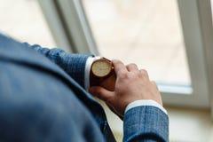 Vue supérieure des mains d'un homme dans un costume regardant une montre-bracelet L'homme d'affaires vérifie le temps sur sa mont photographie stock libre de droits