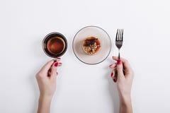 Vue supérieure des mains d'une femme tenant une tasse de thé et de fourchette, sur le Th Photographie stock