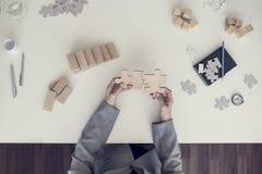 Vue supérieure des mains femelles assemblant deux morceaux en bois de puzzle Photos libres de droits