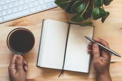 Vue supérieure des mains femelles avec du café et stylo et bloc-notes vide ouvert Vide ou faux pour la conception avec l'espace d photographie stock libre de droits