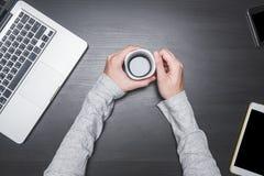 Vue supérieure des mains masculines tenant une tasse de café avec l'ordinateur portable, le comprimé et le téléphone intelligent  Photos stock