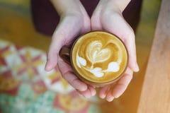Vue supérieure des mains tenant la tasse chaude de latte de café avec la chaîne du hea Photo stock