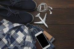 Vue supérieure des messieurs d'habillement d'accessoires à voyager avec le concept de fond de technologie Photographie stock libre de droits