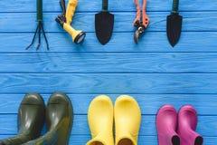 vue supérieure des outils de jardinage disposés et des bottes en caoutchouc colorées sur le bleu Image stock