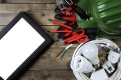 Vue supérieure des outils de travail et des parties du système électriques sur le fond en bois Photographie stock