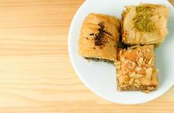 Vue supérieure des pâtisseries de baklava dans différentes saveurs servies sur le Tableau en bois avec l'espace de copie photo stock