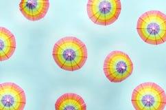 Vue supérieure des parapluies de papier sur le fond bleu lumineux Concept de Ti de vacances, e près de l'océan photo stock