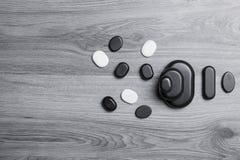 Vue supérieure des pierres noires et blanches de massage sur le conseil gris Photos libres de droits