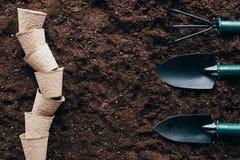 Vue supérieure des pots de fleur vides et des petits outils de jardinage photographie stock