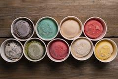 Vue supérieure des saveurs de crème glacée en tasse et écrimage photos stock