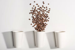 Vue supérieure des tasses de papier jetables blanches avec des grains de café Photos stock