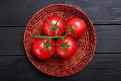 Vue supérieure des tomates dans un panier Tomates rouges mûres, juteuses, colorées sur un fond noir Photos libres de droits