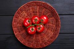 Vue supérieure des tomates dans un panier Tomates rouges mûres, juteuses, colorées sur un fond noir Photographie stock
