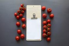 vue supérieure des tomates mûres fraîches avec la feuille et la planche à découper de papier blanc Photo libre de droits