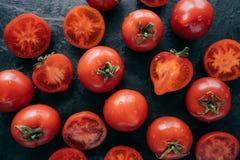 Vue supérieure des tomates rouges fortement détaillées sur le fond noir étant humide Légumes appétissants juteux pour que vous ma images stock