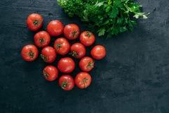 Vue supérieure des tomates rouges fraîches d'héritage et du persil vert sur le fond noir Vitamines de containig de légumes Produi photo libre de droits