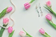 Vue supérieure des tulipes, des boucles d'oreille et de la ficelle roses des perles sur le fond blanc avec l'espace de copie Beau Image libre de droits