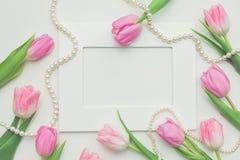 Vue supérieure des tulipes roses, cadre de photo et ficelle des perles sur le fond blanc avec l'espace de copie Beau fond de ress Photographie stock