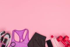 Vue supérieure des vêtements de sport avec les espadrilles et l'équipement de forme physique Photos stock