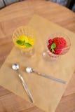 Vue supérieure des verres à vin en cristal complètement du sorbet de fruit Crème glacée colorée avec la menthe décorative sur une Photos libres de droits