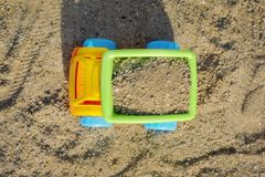 Vue supérieure du camion de déchargeur jaune de jouet en sable sur la plage avec la remorque verte de verseur et les roues bleues photo libre de droits