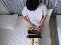 Vue supérieure du jeune homme à l'aide de l'ordinateur portable d'ordinateur sur le lit dans la chambre à coucher photo libre de droits