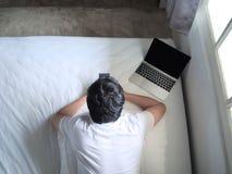 Vue supérieure du jeune homme à l'aide du téléphone et de l'ordinateur portable sur le lit dans la chambre à coucher image libre de droits