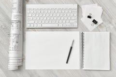 Vue supérieure du lieu de travail du rapporteur avec le clavier, le papier, le stylo, le carnet et l'ébauche roulée Photographie stock libre de droits