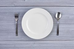 Vue supérieure du plat blanc avec la fourchette et la cuillère Image stock