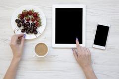 Vue supérieure, espace de travail féminin avec les mains femelles, smartphone, comprimé, baies et latte sur le fond en bois blanc Photo stock