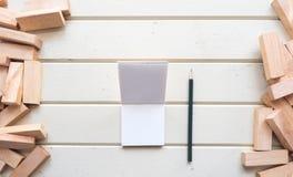 Vue supérieure et carnet de bloc en bois avec le crayon sur le backgroun en bois Images libres de droits