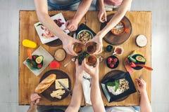 Vue supérieure, groupe de personnes s'asseyant à la table avec la nourriture, appréciant une boisson Photographie stock libre de droits