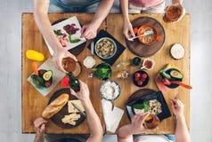 Vue supérieure, groupe de personnes s'asseyant à la table avec la nourriture, appréciant une boisson Image stock