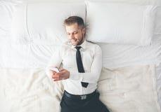 Vue supérieure Homme d'affaires bel se trouvant sur le service de mini-messages de lit de son smartphone Photographie stock libre de droits