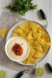 Vue supérieure, immersion de fromage faite maison avec les puces de tortilla jaunes au-dessus du fond en bois blanc Configuration photos stock